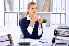 Lycklig affärskvinna eller kvinnligrevisor som har några minuter för kaffe och nöje på arbetsplatsen Arkivbild