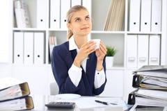 Lycklig affärskvinna eller kvinnligrevisor som har några minuter för kaffe och nöje på arbetsplatsen Arkivfoto