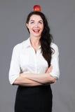 Lycklig affärskvinna med äpplet på huvudet Fotografering för Bildbyråer