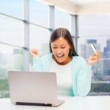 Lycklig affärskvinna med bärbara datorn och kreditkorten Royaltyfria Bilder