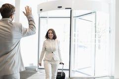 Lycklig affärskvinna med bagage som går in mot den manliga kollegan i konventcentrum Royaltyfri Bild