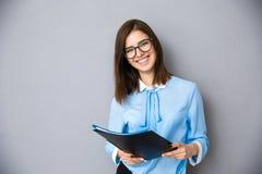 Lycklig affärskvinna med mappar över grå bakgrund Royaltyfria Foton