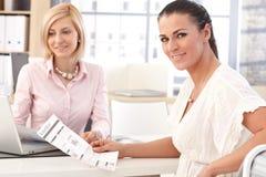 Lycklig affärskvinna på kontoret med affärsrapporten Arkivfoton