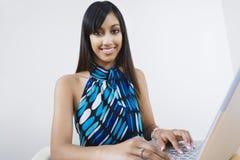 Lycklig affärskvinna som använder bärbara datorn royaltyfria bilder