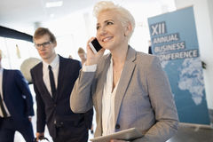 Lycklig affärskvinna som använder den smarta telefonen på konventcentret Arkivbild