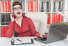 Lycklig affärskvinna som använder mobiltelefonen och arbete med bärbara datorn arkivfoto