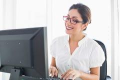 Lycklig affärskvinna som arbetar på hennes skrivbord Arkivfoto