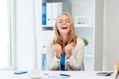 Lycklig affärskvinna som firar framgång på kontoret arkivbilder