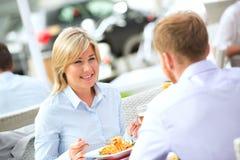 Lycklig affärskvinna som har mat med den manliga kollegan på den utomhus- restaurangen royaltyfri bild