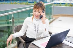 Lycklig affärskvinna som i regeringsställning talar på den tele mobiltelefonen hemma royaltyfria foton