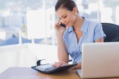 Lycklig affärskvinna som kallar med hennes mobiltelefon och ser Fotografering för Bildbyråer