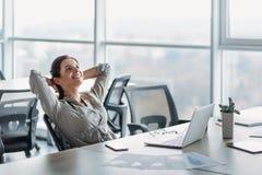 Lycklig affärskvinna som kopplar av med händer bak huvudet på kontorsskrivbordet Dagdrömma begrepp arkivfoto