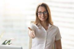 Lycklig affärskvinna som når handen för handskakning royaltyfri bild