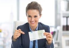 Lycklig affärskvinna som pekar på pengarpacke Royaltyfri Fotografi