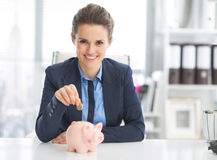 Lycklig affärskvinna som sätter myntet in i spargrisen Royaltyfri Fotografi