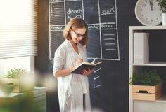 Lycklig affärskvinnakvinna på skolförvaltningen med schemaplanläggning Arkivbild