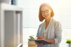 Lycklig affärskvinnakvinna på skolförvaltningen med schemaplanläggning royaltyfri foto