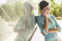 Lycklig affärskvinnaUsing Cellphone While benägenhet på väggen royaltyfri foto