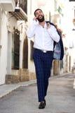 Lycklig affärsman för full längd som går på gatan och talar på den smarta telefonen Royaltyfria Foton