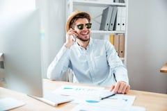 Lycklig affärsman i hatt som i regeringsställning talar på mobiltelefonen Fotografering för Bildbyråer