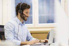 Lycklig affärsman i kontoret på telefonen, hörlurar med mikrofon, Skype Fotografering för Bildbyråer