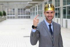 Lycklig affärsman med ett utrymme för krona i regeringsställning royaltyfri bild