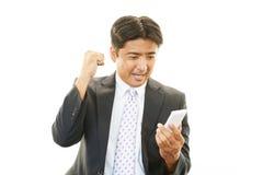 Lycklig affärsman med mobiltelefonen royaltyfri foto