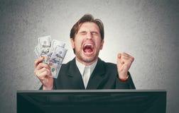 Lycklig affärsman med pengar i hand och dator Royaltyfria Bilder