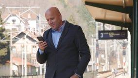 Lycklig affärsman With Mobile Phone i drev för handtextväntan i järnvägsstation arkivfoton
