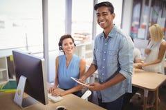 Lycklig affärsman- och kvinnligkundtjänstrepresentant som i regeringsställning arbetar Arkivfoton