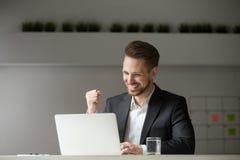 Lycklig affärsman som firar lookin för seger för affärsframgång online- arkivfoto