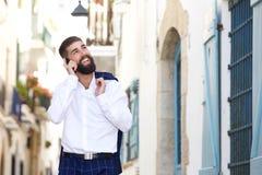 Lycklig affärsman som går på gatan som talar på den smarta telefonen Arkivfoton