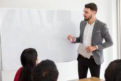 lycklig affärsman som gör en presentation på whiteboard framstickande som framlägger strategi av marknadsföringen till målet av f royaltyfria foton