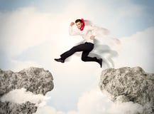 Lycklig affärsman som hoppar över en klippa royaltyfri bild