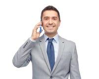 Lycklig affärsman som kallar på smartphonen Fotografering för Bildbyråer