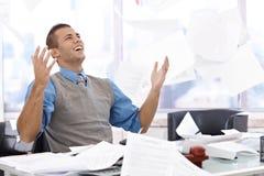 Lycklig affärsman som kastar förlagor Arkivfoto