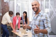 Lycklig affärsman som ler på kameran som ger upp tummar arkivfoton