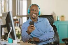Lycklig affärsman som lyssnar till hörlurar Royaltyfri Foto