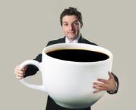 Lycklig affärsman som rymmer den roliga enorma överdimensionerade koppen av svart cof Fotografering för Bildbyråer