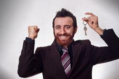 Lycklig affärsman som rymmer en hustangent Royaltyfria Bilder