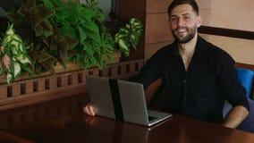 Lycklig affärsman som ser kameran som arbetar med bärbara datorn och talar i ultrarapid arkivfilmer