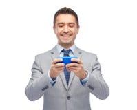 Lycklig affärsman som smsar på smartphonen Arkivfoto