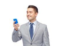 Lycklig affärsman som smsar på smartphonen Royaltyfri Bild