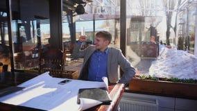 Lycklig affärsman som talar vid smartphonen om utkastprojekt på kafét och tycker om framgång n stock video