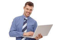 Lycklig affärsmanholdingbärbar dator Arkivbild
