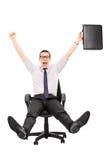 Lycklig affärsmanridning i en kontorsstol arkivbild