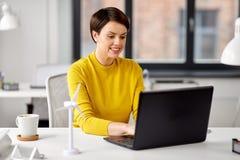 Lycklig aff?rskvinna med b?rbara datorn som arbetar p? kontoret royaltyfri foto