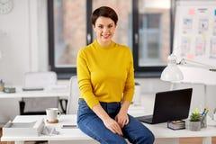 Lycklig aff?rskvinna som sitter p? skrivbordet p? kontoret arkivfoto
