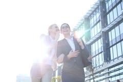 Lycklig affärskvinna som viskar i kollegas öra utanför kontorsbyggnad på solig dag Arkivbild
