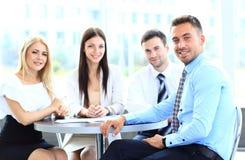 Lycklig affärsman med kollegor på en konferens Arkivfoto